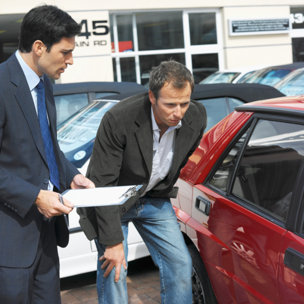 Salesman with a clipboard assisting a male customer buying a car