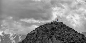 Silhouette of a girl with backpack on huge mountain. Very far. Epic black-and-white photo.