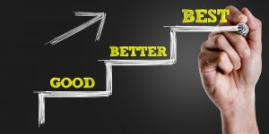 Hand writing the text: Good – Better – Best