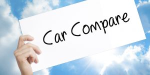 Car Compare Sign on white paper. Man Hand Holding Paper with text. Isolated on sky background