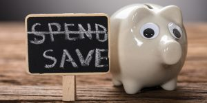 Closeup Of Piggybank By Spend Save Sign On Wood