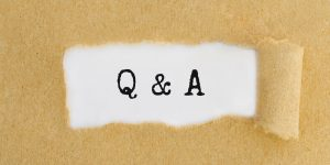 Text Q and A appearing behind ripped brown paper.