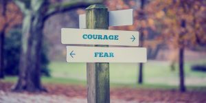 Rustic wooden sign in an autumn park with the words Courage – Fear