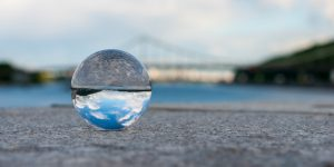 Glass transparent ball on bridge background and grainy surface. With empty space